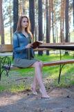 Jonge vrouw die een boek lezen en bij het park ontspannen stock afbeeldingen