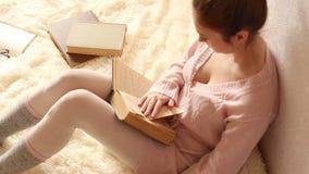 Jonge vrouw die een boek lezen en koffie drinken stock videobeelden