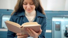 Jonge vrouw die een boek in metroplatform lezen stock video