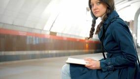 Jonge vrouw die een boek in metroplatform lezen stock footage