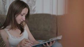 Jonge vrouw die een boek op de laag lezen stock videobeelden