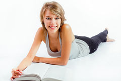 Jonge vrouw die een boek op de vloer lezen royalty-vrije stock afbeeldingen