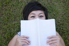 Jonge vrouw die een boek op het gebied leest Stock Afbeelding