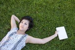 Jonge vrouw die een boek op het gebied leest royalty-vrije stock foto