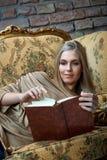 Jonge vrouw die een boek thuis op bank lezen stock foto's