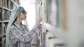 Jonge vrouw die een boek van boekenrek in universitaire bibliotheek selecteren stock videobeelden