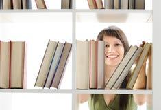 Jonge Vrouw die een boek zoekt Stock Foto's