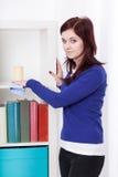 Jonge vrouw die een boekenkast bestrooien stock afbeeldingen