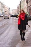 Jonge vrouw die een cabine in de stad probeert te begroeten Royalty-vrije Stock Afbeelding