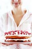 Jonge vrouw die een cake houdt Stock Afbeeldingen