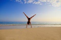 Jonge vrouw die een cartwhee doet Stock Foto