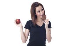 Jonge vrouw die een chocoladereep bijten en een verse appel vangen Stock Foto's