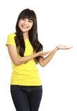 Jonge vrouw die een denkbeeldig product toont Stock Afbeeldingen