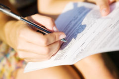 Jonge vrouw die een document ondertekent Stock Afbeeldingen