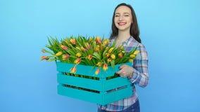 Jonge vrouw die een doos van verse tot bloei komende tulpen houden stock videobeelden