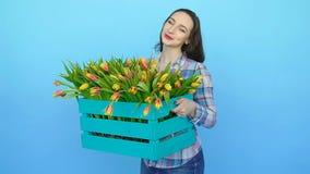Jonge vrouw die een doos van verse tot bloei komende tulpen houden stock footage