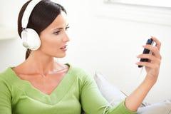 Jonge vrouw die een draagbare muziekspeler houden Stock Afbeeldingen