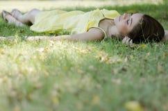 Jonge vrouw die een dutje in een park neemt Stock Foto's