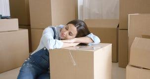 Jonge vrouw die een dutje op een bruin karton nemen Royalty-vrije Stock Foto's