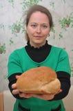 Jonge vrouw die een eigengemaakt brood houden Stock Afbeelding