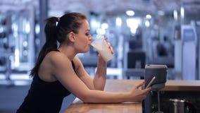 Jonge vrouw die een eiwitschok drinken en de telefoon bekijken stock videobeelden