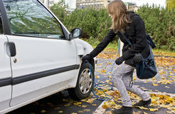 Jonge Vrouw die in een Elektrische Auto stopt Stock Foto