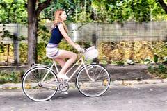 Jonge vrouw die een fiets berijden stock foto's