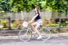 Jonge vrouw die een fiets berijden stock afbeelding
