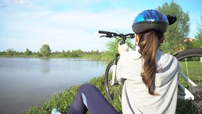 Jonge vrouw die een fiets berijden door het park op de achtergrond van een meer of een rivier stock video
