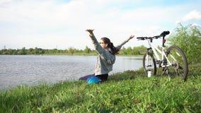 Jonge vrouw die een fiets berijden door het park op de achtergrond van een meer of een rivier stock videobeelden