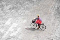 Jonge vrouw die een fiets in de straat, de de zomertijd en het levensstijlconcept berijden lege exemplaarruimte stock fotografie