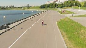 Jonge vrouw die een fiets in openlucht in de zomer berijden Rivierdijk Milieuvriendelijk vervoer Het lucht schieten stock videobeelden