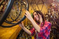 Jonge vrouw die in een fietsreparatiewerkplaats werken Stock Foto's