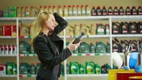 Jonge vrouw die een fles motorolie houden Het meisje kiest aan autoolie stock videobeelden
