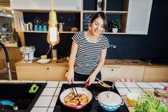 Jonge vrouw die een gezonde maaltijd in huiskeuken koken Het maken van diner op keukeneiland die zich door inductiehaardplaat bev stock afbeelding