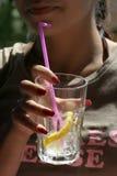 Jonge vrouw die een glas limonade houdt royalty-vrije stock afbeeldingen