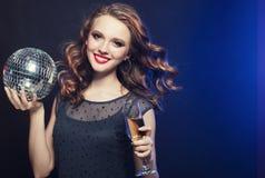 Jonge vrouw die een glas van wijn en discobal houden bij nachtclub royalty-vrije stock fotografie