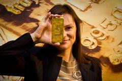 Jonge vrouw die een gouden bar houden Royalty-vrije Stock Foto