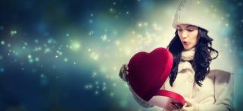 Jonge vrouw die een grote doos van de hartgift houden Stock Foto's