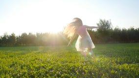 Jonge vrouw die een handstand in openlucht doen bij zonsondergangweide stock video