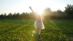 Jonge vrouw die een handstand in openlucht doen bij zonsondergangweide stock footage