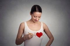 Jonge vrouw die een hart trekken op haar t-shirt royalty-vrije stock afbeeldingen