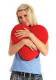 Jonge vrouw die een hart-vormig hoofdkussen koestert stock foto