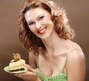 Jonge vrouw die een heerlijk stuk van cake steunt royalty-vrije stock afbeeldingen