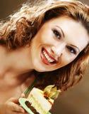 Jonge vrouw die een heerlijk stuk van cake steunt Royalty-vrije Stock Foto