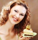 Jonge vrouw die een heerlijk stuk van cake steunt royalty-vrije stock fotografie