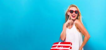 Jonge vrouw die een het winkelen zak houdt met Stock Foto's