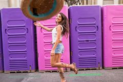 Jonge vrouw die een hoed werpen Stock Foto's