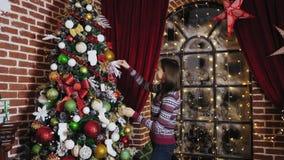 Jonge vrouw die een Kerstboom thuis verfraaien stock video