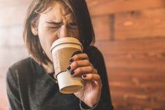 Jonge vrouw die een koffie drinken en haar tong branden royalty-vrije stock afbeeldingen